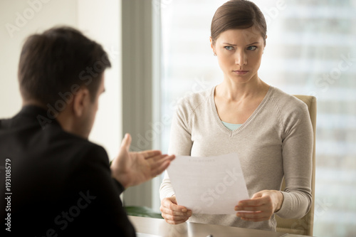 Fotografering  Millennial businesswoman with skeptical facial expression holding contract document and listening unconvincing offer of business partner