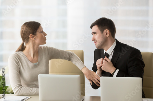 Photo Man with deliberately sad facial expression asking female coworker to help with difficult project to leave work earlier, inviting colleague to date