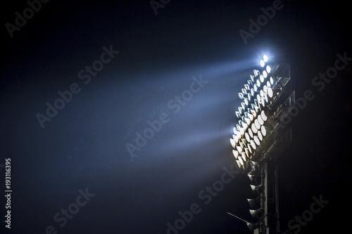Obraz Light tower lit at a stadium during nightime. - fototapety do salonu