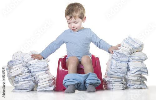 Happy baby boy sitting on chamber pot tearing down diaper piles Fototapet
