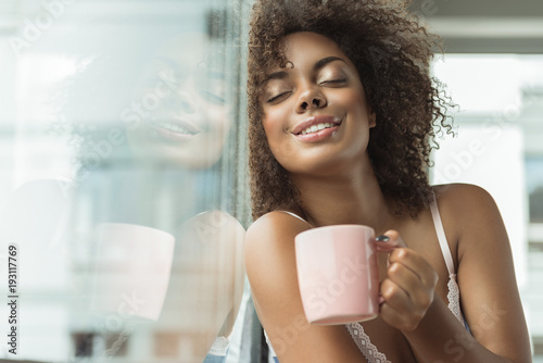 Obraz Portrait of cheerful african woman expressing pleasure while drinking cup of delicious beverage in room - fototapety do salonu