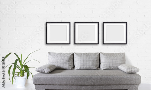 Three blank frames set over modern couch, and yucca plant in white ...