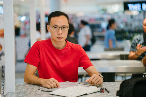 A middle-aged Asian man working on his journal. He is writing seriously and concentrating on his task for the day.