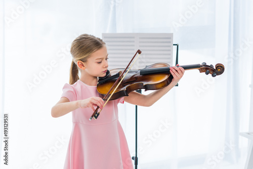 Fotografia cute little child in pink dress playing violin at home