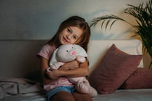Portrait Of Cute Kid With Toy Resting On Sofa