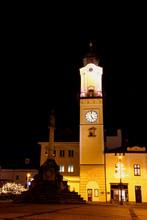 Floodlit Clock Tower At Night Illuminated By Exterior Facade Lights With Mary's Plague Column In Banska Bystrica Main Square, Hodinova Veza, Namestie Slovenskeho Narodneho Povstania, Slovakia Europe