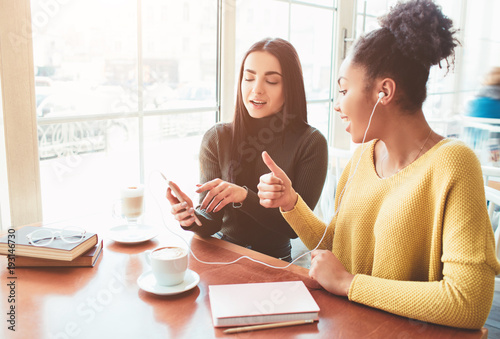 Fotografie, Obraz  cheerful and attractive girls are sitting near the bright window in cafe