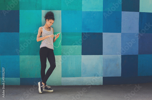 African-american woman posing, leaning on bright wall