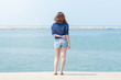 Back view of Asian woman traveler in blue casual and jean shorts standing on the stone terrace and looking around the sea ocean.