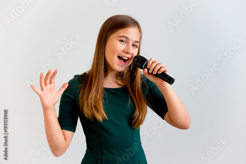 Obraz na plátně Girl singing with a microphone