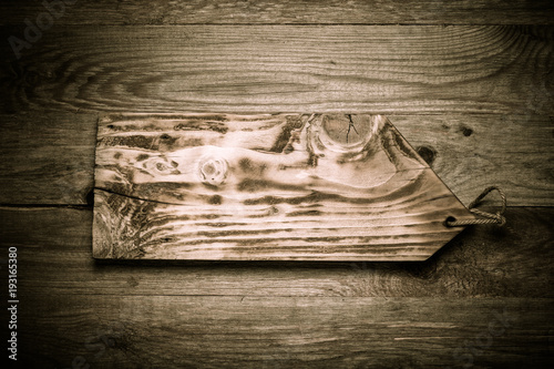 Foto op Plexiglas Stenen in het Zand Handmade burned cutting board on a wooden rustic texture for background. Rough weathered wooden board. Toned