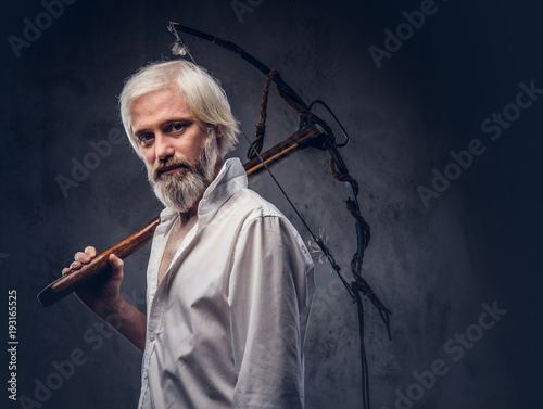 27fed60917f Studio portrait of a smiling handsome old man with a gray beard and white  shirt holding