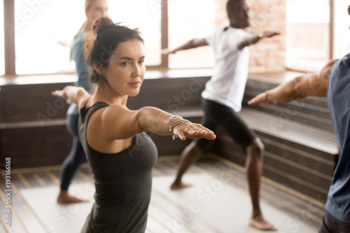 Recess Fitting Yoga school Attractive yogi woman and a group of young sporty people practicing yoga lesson, standing in Warrior two exercise, Virabhadrasana 2 pose, working out, indoor close up, studio