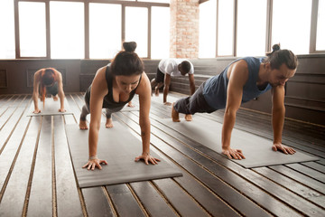 Group of young sporty people practicing yoga lesson standing in Plank pose, doing Push ups or press ups exercise, working out, indoor full length, studio floor