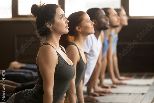 Fotografia  Group of young sporty afro american and caucasian people practicing yoga lesson,