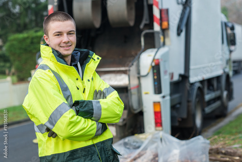 Valokuva  young garbage collector near truck