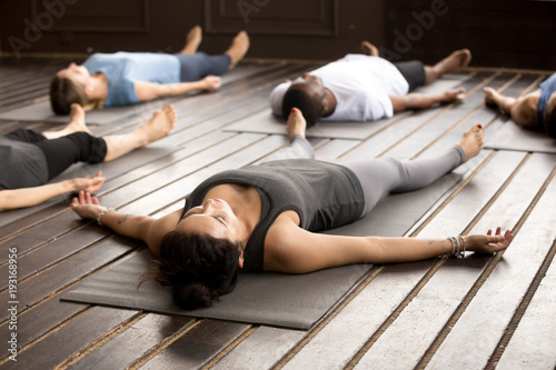 Poster Ecole de Yoga Group of young afro american and caucasian sporty people practicing yoga lesson lying in Dead Body pose, Savasana exercise, working out, resting after practice, indoor close up, studio