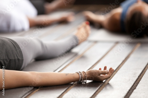 Poster Ecole de Yoga Group of young sporty people practicing yoga, lying in Corpse pose, Savasana exercise, working out, resting after practice, female hand with wrist bracelets close up, studio. Healthy lifestyle concept