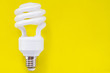 canvas print picture - Fluorescent light bulb on yellow background, technology that contains polluting gases