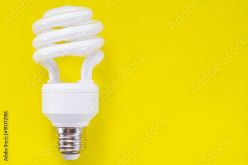 Photo  Fluorescent light bulb on yellow background, technology that contains polluting