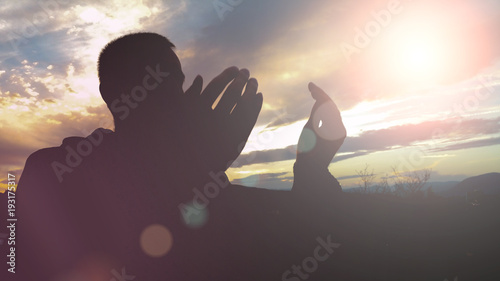 Fotografie, Obraz  Silhouette of young muslim man praying during sunset