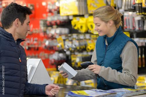 Foto female hardware store seller scanning clients item