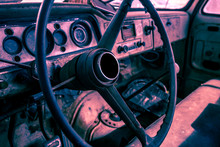 Inerior Of Old Abandoned Truck, Grunge Background With Rusty Dashboard And Driving Wheel