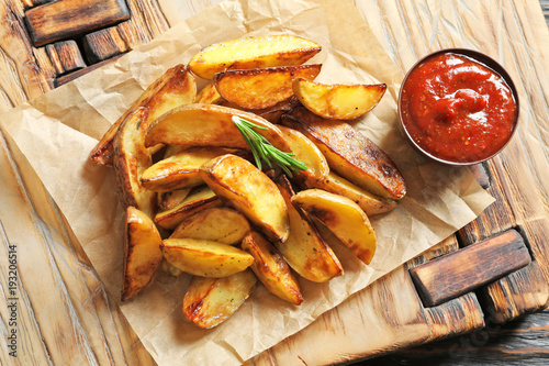Tasty potato wedges and tomato sauce on wooden board