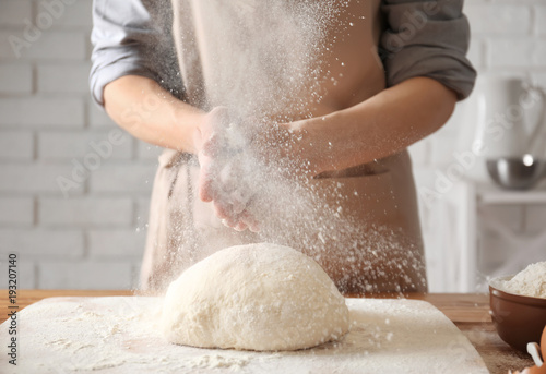 Photo  Woman clapping and sprinkling flour over dough on table