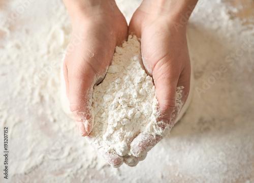 Fototapeta Woman holding wheat flour above table, closeup obraz
