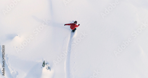 plakat Snowboarding Overhead Top Down View of Snowboarder Riding Through Fresh Powder Snow Down Ski Resort or Backcountry Slope - WInter Extreme Sports Background