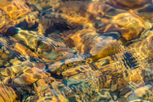 Texture Of Shallow Water Over Golden Brown River Rocks Creates A Unique Abstract Effect In Warm Tones