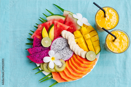Tropical fruits assortment on a white plate with palm tree leaf with mango smoothie. Top view. Copy space