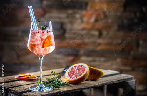 Foto op Plexiglas Cocktail Cocktail drink on a old wooden board. Alcoholic beverage with tropical fruits red pepper herb and ice