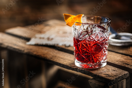 Photo sur Aluminium Cocktail Cocktail Negroni on a old wooden board. Drink with gin, campari martini rosso and orange