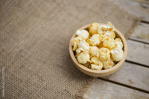 Salted Popcorn In Round Wooden Bowl On Hessian Fabric Background