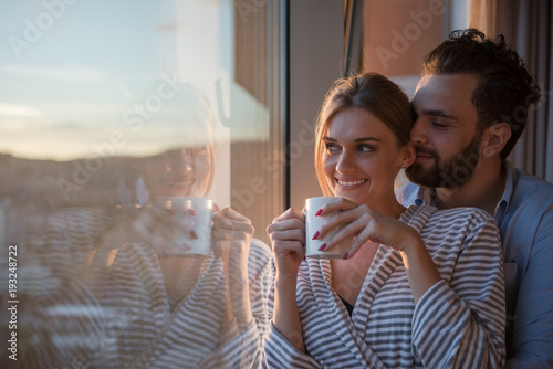 young couple enjoying evening coffee by the window Fototapet