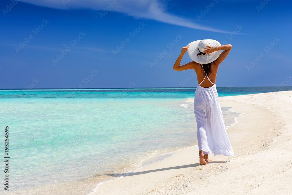 Fototapeta Elegante Frau in weiß läuft über einen tropischen Strand und genießt ihren Urlaub