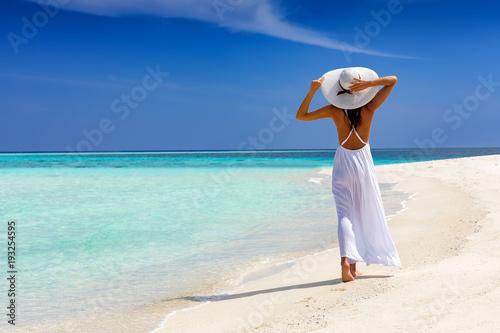 Fototapeta Elegante Frau in weiß läuft über einen tropischen Strand und genießt ihren Urlaub obraz