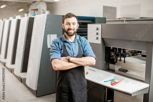 Fotografía  Portrait of a handsome typographer standing at the printing manufacturing with o