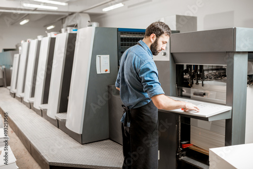 Fotografía  Printing operator working with offset machine at the printing manufacturing