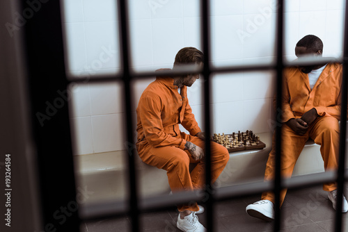 Fotografía multiethnic prisoners playing chess behind prison bars