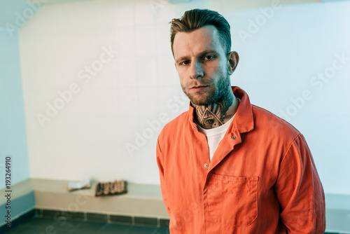 tattooed prisoner looking at camera in prison cell Fototapet