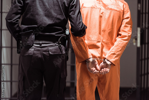 Fotografering rear view of prison officer leading prisoner in handcuffs