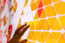 Tessellation Of A Plane With Yellow, Orange And Red Colored Triangles On A White Background. Mathematical And Artistic Game To Cover A Surface With Geometric Shapes. Kids Play Math Games With Hand