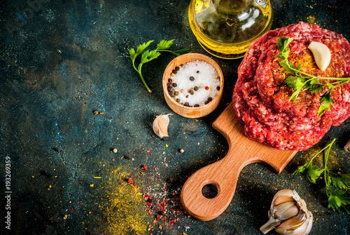 Plakat Surowi hamburgerów cutlets z solą, pieprzem, olejem, ziele i pikantnością, na zmroku stole, kopii astronautyczny odgórny widok