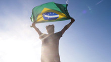 Young Man Holding Brazilian National Flag To The Sky With Two Hands At The Beach At Sunset Brazil