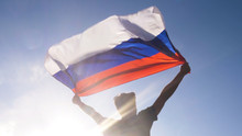 Young Man Holding Russian National Flag To The Sky With Two Hands At The Beach At Sunset Russia