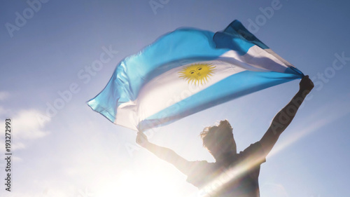 Fotomural Young man holding argentinian national flag to the sky with two hands at the bea