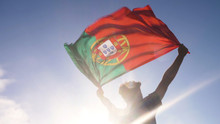 Young Man Holding Portuguese National Flag To The Sky With Two Hands At The Beach At Sunset Portugal